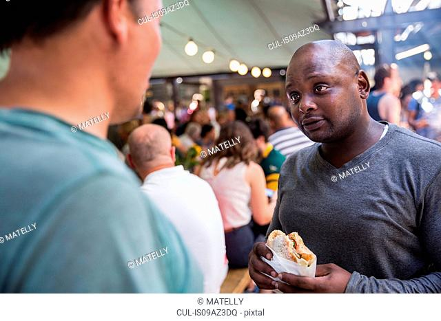 Male customers chatting and eating burgers at cooperative food market stall