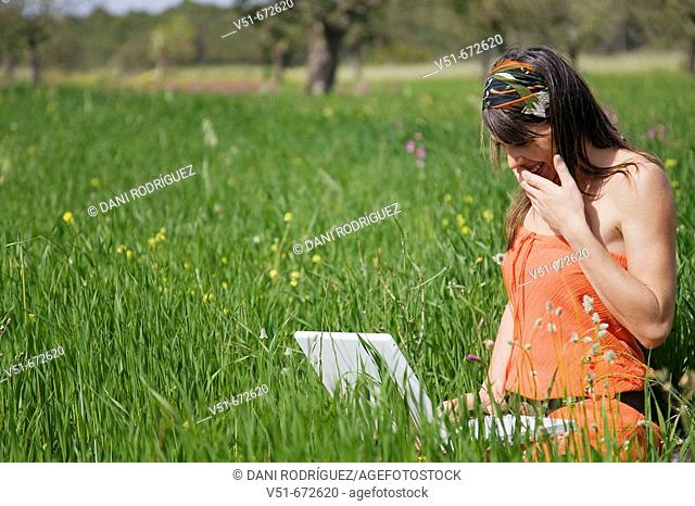 Woman using laptop in the countryside