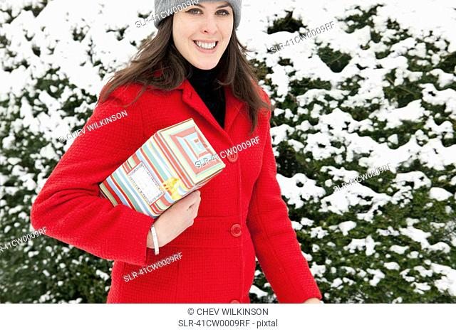 Woman carrying wrapped gift in snow