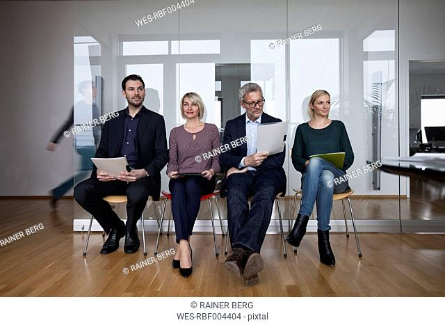 Four people sitting in a row, waiting in office
