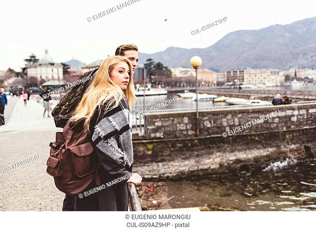 Young couple looking over their shoulders at lakeside, Lake Como, Italy