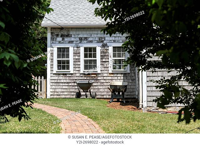 Wheelbarrows by a shingled home in Vineyard Haven, Martha's Vineyard, Massachusetts, United States, North America