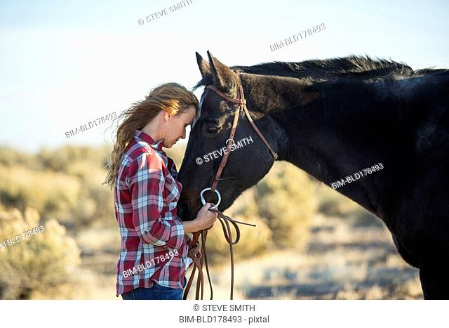 Caucasian woman hugging horse in field
