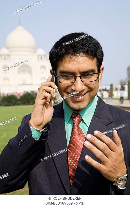 Indian businessman talking on cell phone at the Taj Mahal