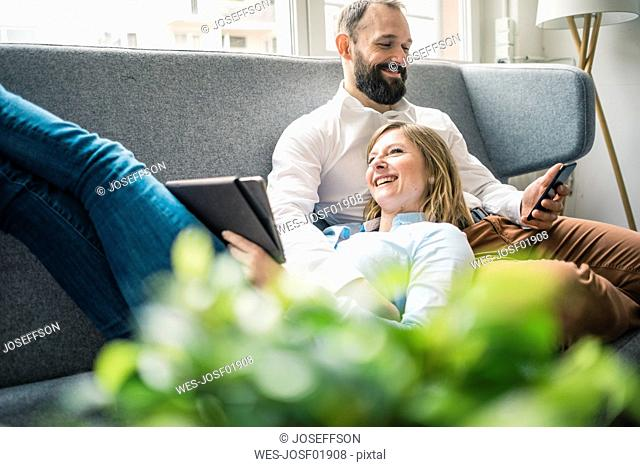 Smiling couple using tablet and cell phone on couch