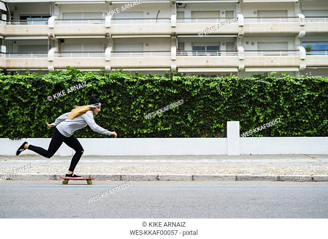 Young woman skateboarding on street