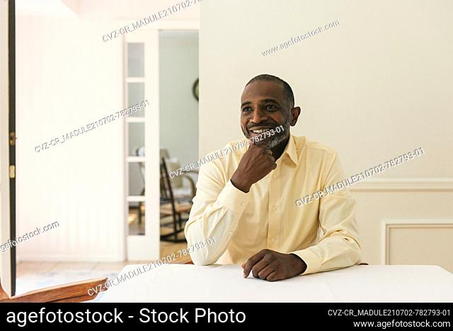 Happy man smiling and looking off camera in his bright home table