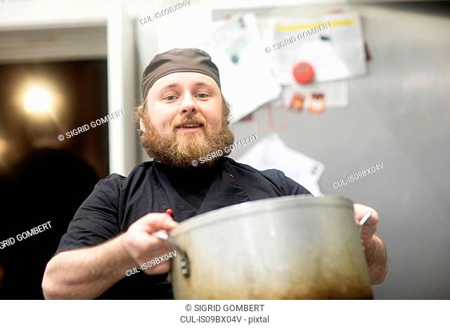 Fast food worker carrying large pan in commercial kitchen, portrait