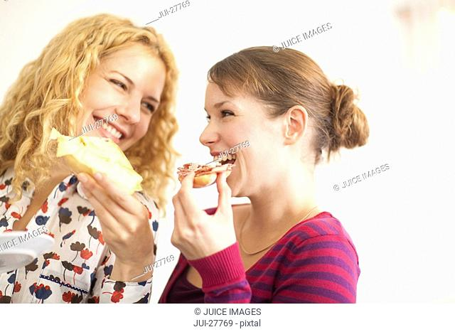 Two women eating and laughing