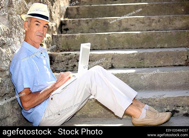 mature man doing computer outside at the foot of stairs