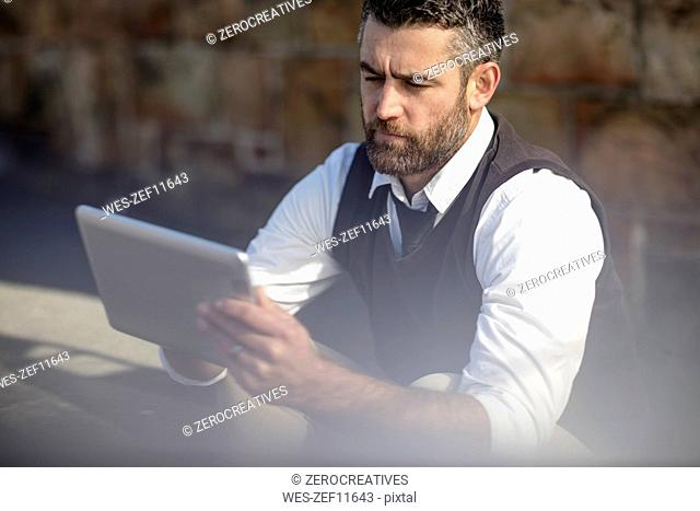 Man looking at tablet outdoors