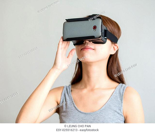 Young woman with hand holding virtual reality device