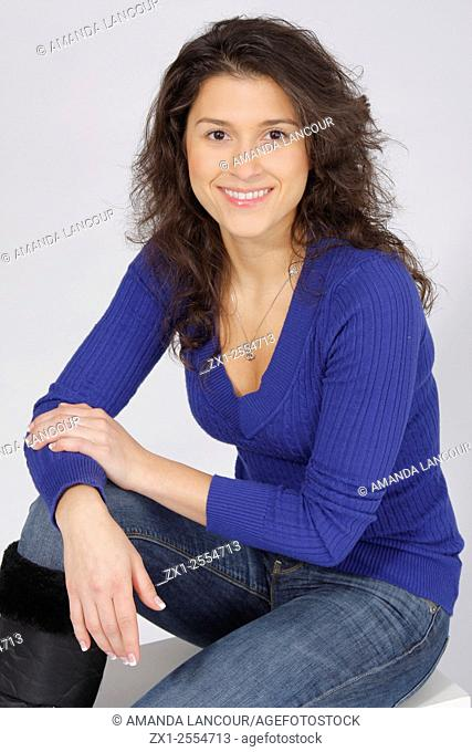 Portrait of a women in a blue long sleeve v-neck sweater in jeans on a white backdrop