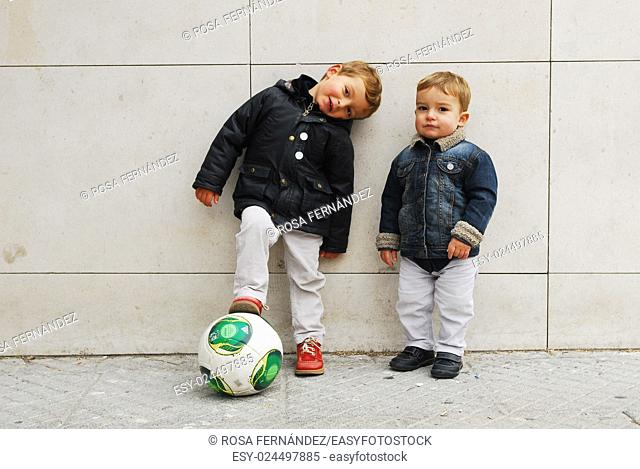 Two baby boys playing with a football at the street, Madrid, Spain