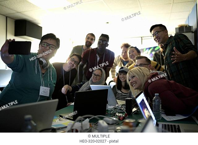 Young hackers taking selfie working hackathon at laptops