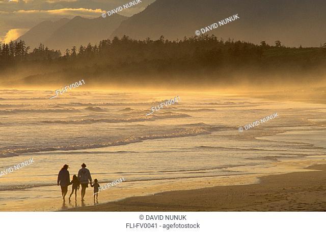 Family walking along beach at sunset, Long Beach at sunset, Pacific Rim Nat Park, BC