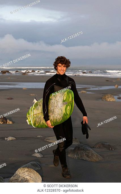 Surfer with board on beach, Southeast Alaska; Yakutat, Alaska, United States of America