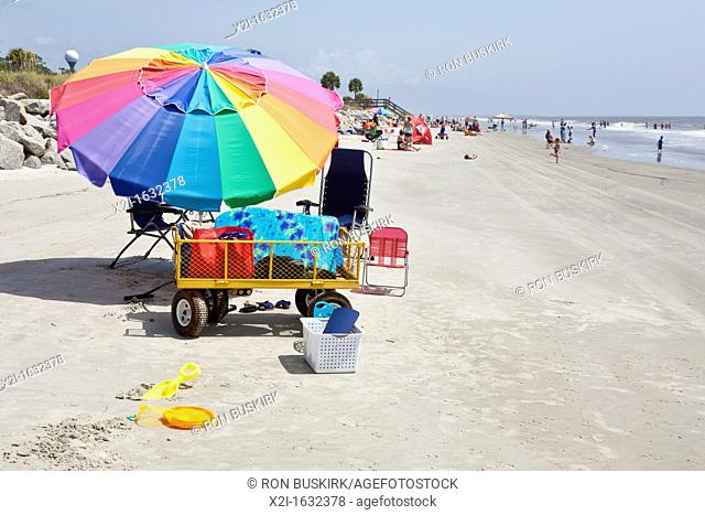 Sunbathers and colorful beach umbrellas on the public beach at Jekyll Island, Georgia