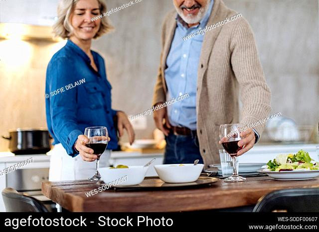 Mature couple raising wine glasses during dinner in kitchen at home