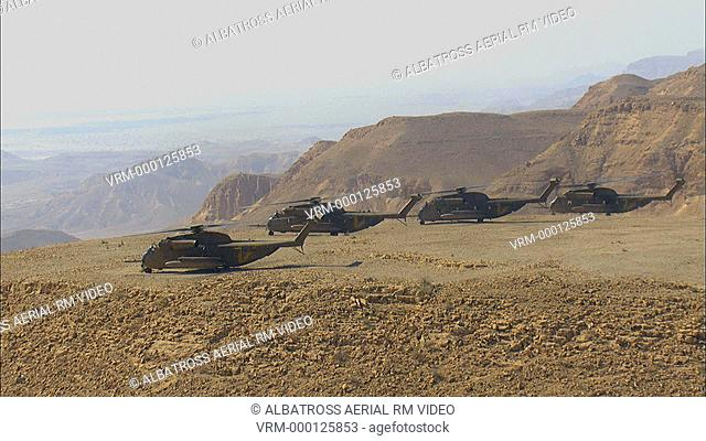 Aerial footage of three Military Helicopters above the Desert. Could be black hawk helicopter or a CH-53 helicopter