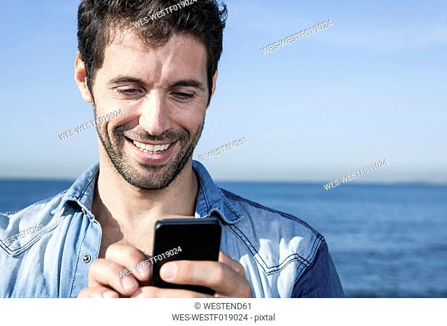 Spain, Mid adult man using smart phone, smiling