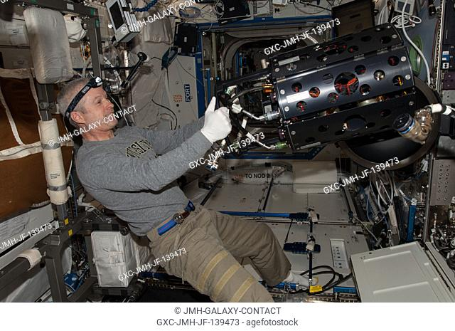 NASA astronaut Steve Swanson, Expedition 40 commander, works with the Multi-user Drop Combustion Apparatus (MDCA) inside the Combustion Integrated Rack (CIR) in...