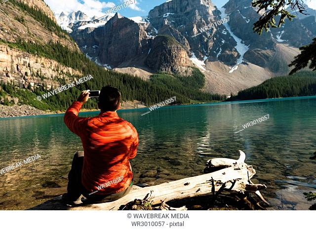 Rear view of man taking picture with mobile phone