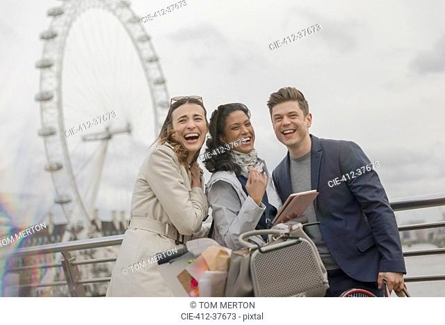 Portrait laughing friends with digital tablet near Millennium Wheel, London, UK
