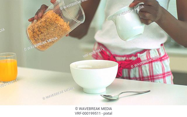 Woman pouring milk and cereal into bowl