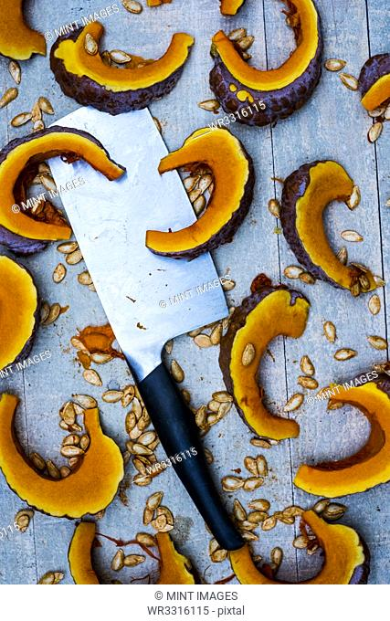 High angle close up of cleaver and slices of pumpkin on blue background