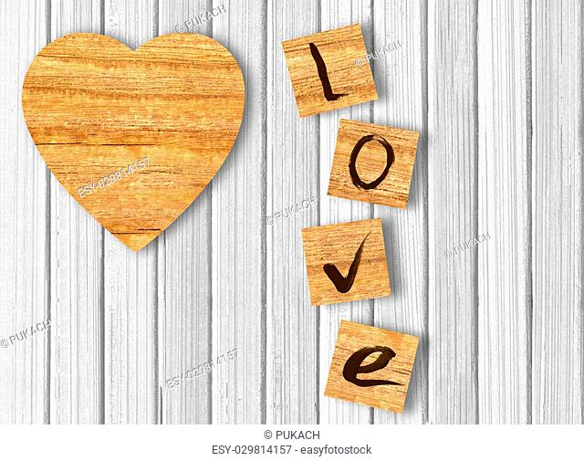 Wood heart on white wooden background. Love cast out of wood kubik