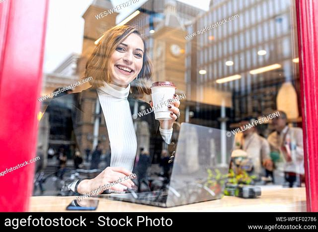 Portrait of happy businesswoman using laptop at a cafe in the city