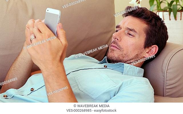 Man lying on couch answering his phone