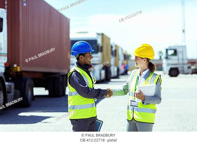 Worker and businesswoman shaking hands near trucks and cargo containers