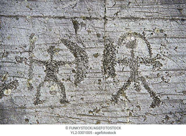 Prehistoric Petroglyph, rock carving, of two warriors with shileds and a spear carved by the Camunni people in the iron age between 1000-1600 BC