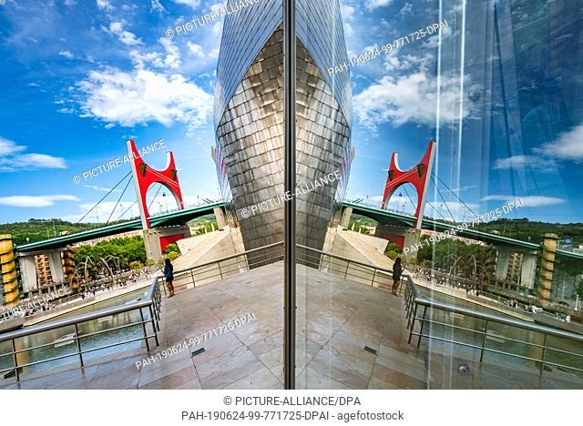 23 June 2019, Spain, Bilbao: The Guggenheim Museum in Bilbao is partly reflected in the glass and titanium façade. Next to it is the Puente La Salve