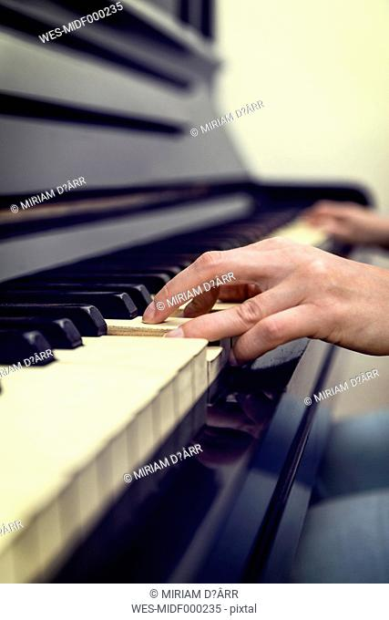 Hands of woman on old piano