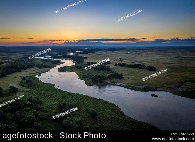 dawn over Dismal River meandering through Nebraska Sandhills at Nebraska National Forest, aerial view of summer scenery
