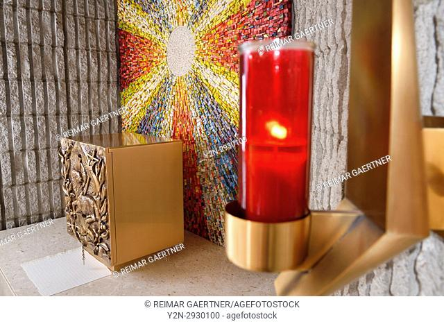 Red Sanctuary Lamp or Eternal Flame at the Tabernacle with bronze Lamb of God bas relief at side altar with sunburst mosaic in Catholic church