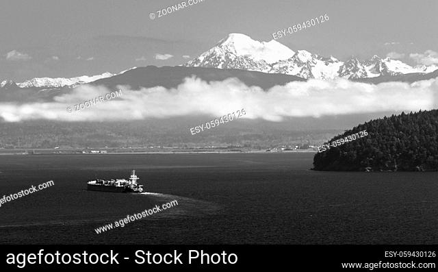 a large ship sets out in Puget Sound with Mt Baker overlooking