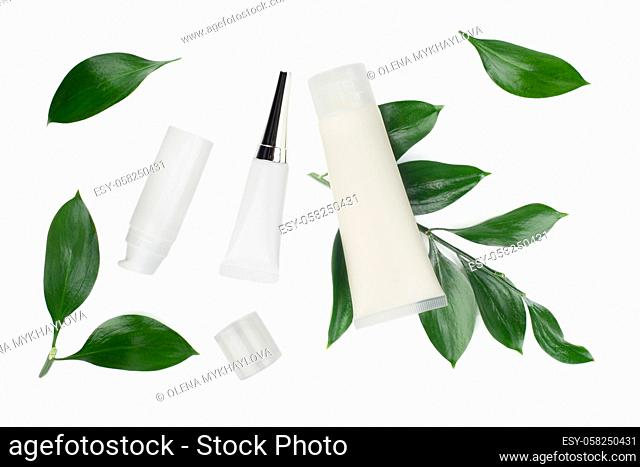 Flat lay view at white cosmetic bottles and containers with green leaves on white table