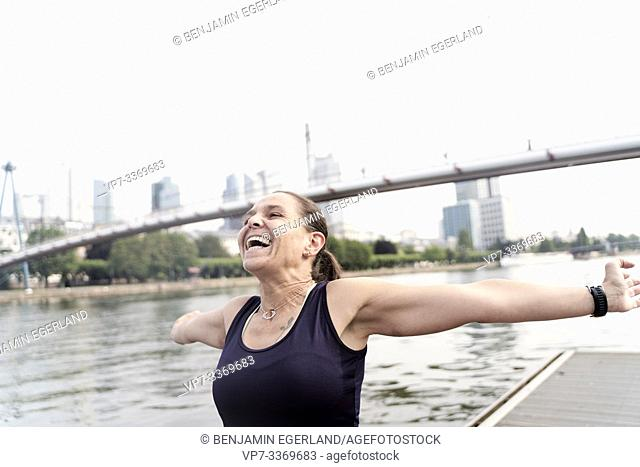 mid adult sports woman with open arms, enjoying training at riverside Main, in Frankfurt, Germany