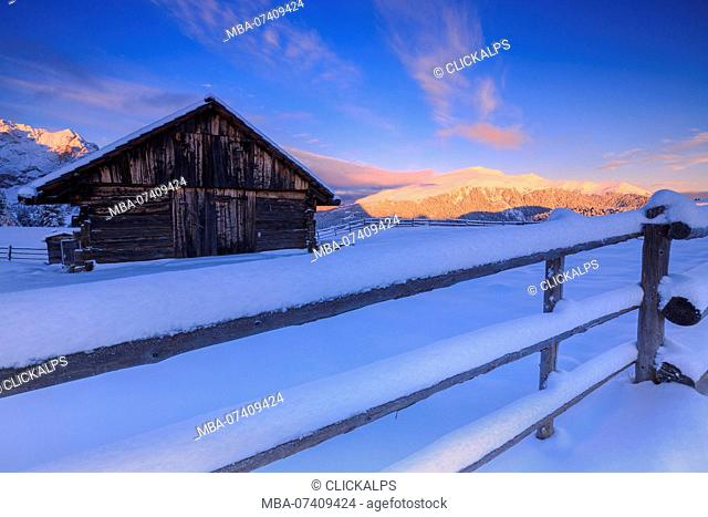 Old snow-covered hut during sunrise. Erbe Pass, Funes Valley, South Tyrol, Dolomites, Italy