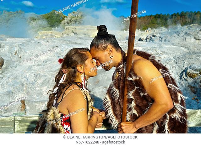 A Maori man with ta moko facial tattoo and woman doing hongi traditional Maori greeting with the Pohutu Geyser behind, Te Puia New Zealand Maori Arts & Crafts...