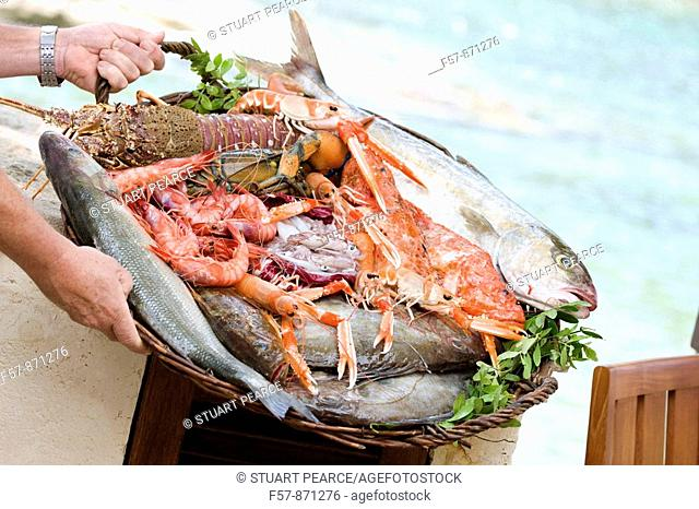 Server holding a basket of fresh fish in Mallorca, Spain