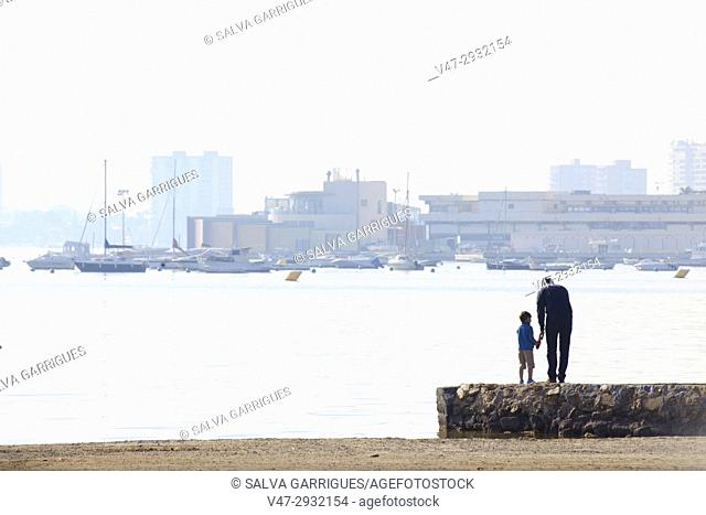 Father and son contemplating the sea on the beach of San Pedro del Pinatar, Murcia, Spain