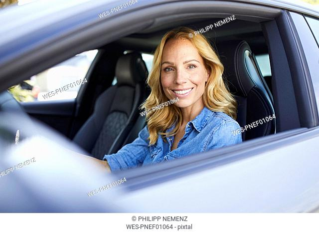 Portrait of smiling woman driving car looking out of window