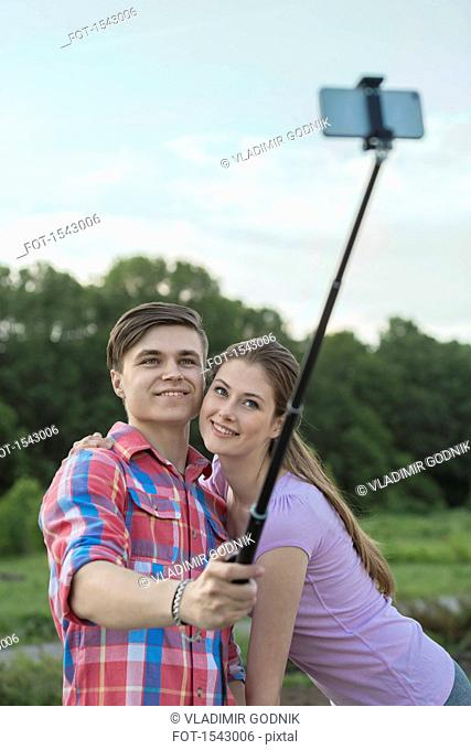 Happy young couple taking selfie through monopod at park