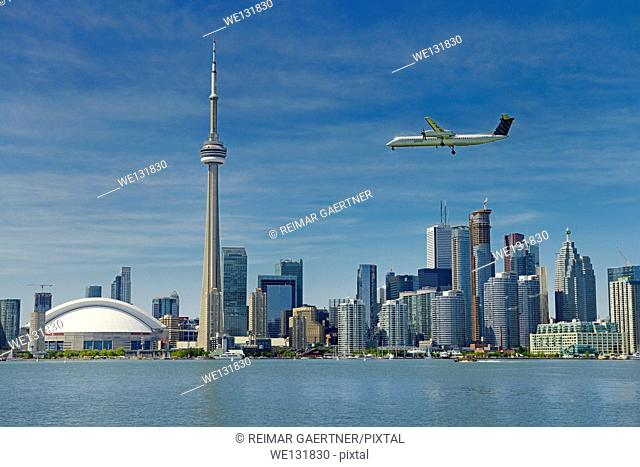 Toronto skyline with Rogers Centre CN Tower condo and financial towers and Porter airplane landing on Island Airport