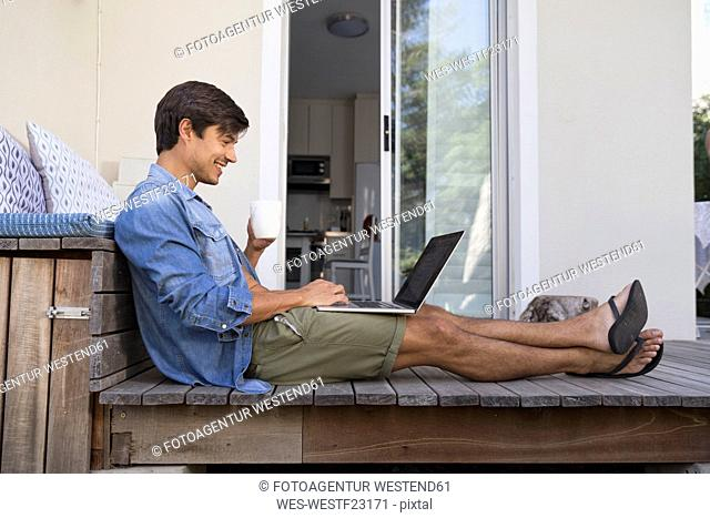 Man sitting on terrace using laptop